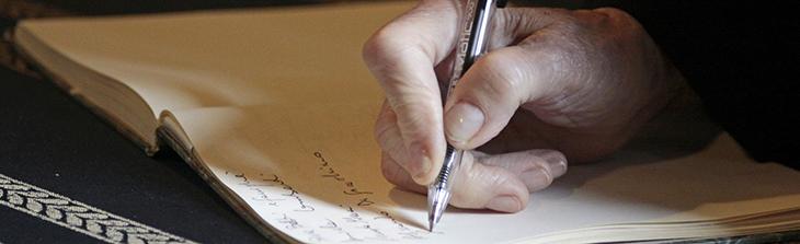 Nahaufnahme. Die Hand einer älteren Person trägt etwas in ein Buches ein.