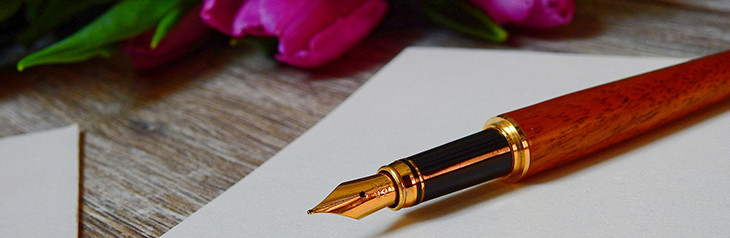 Großaufnahme eines Füllers mit goldener Feder und einem Griff mit Holz-Optik. Er liegt auf einem leeren Blatt Papier, dahinter sind Blumen zu erkennen.