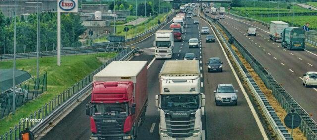 Eine Autobahn auf der Lkw und Autos fahren