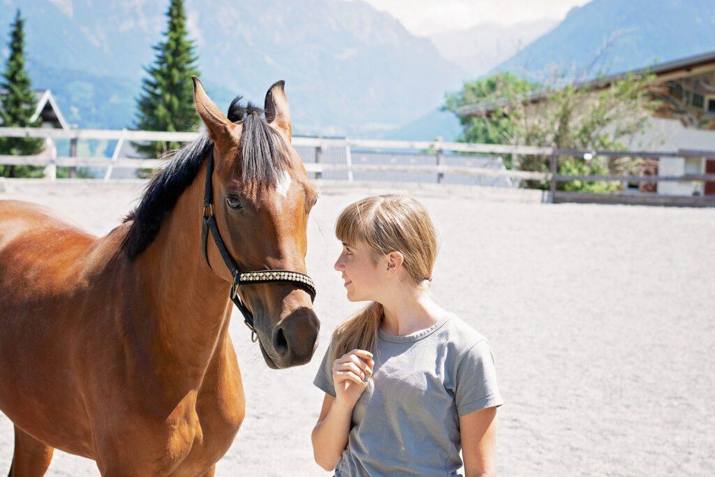 Eine junge Frau spricht mit einem Pferd