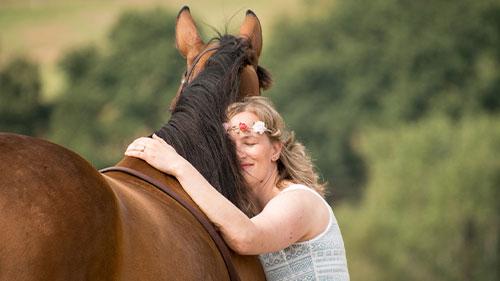 Eine Frau umarmt ein Pferd