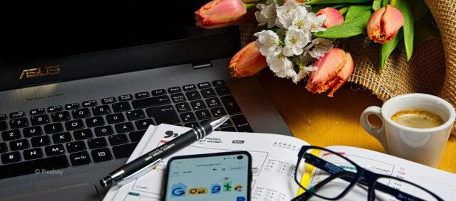 Blumen und Kaffe auf einem Schreibtisch
